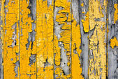 Yellow cracked paint on wooden boards — Stock Photo