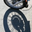 Stock Photo: Front wheel of motorcycle and shade