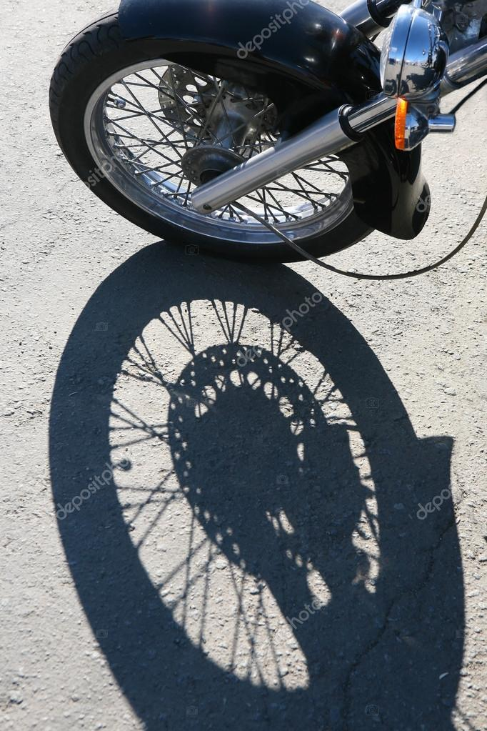 Front wheel of motorcycle and shade on asphalt — Stock Photo #14433707