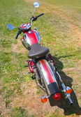 Red motorcycle on meadow — Stock Photo
