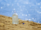 Bottle with water on the sandy coast — Stock Photo