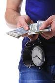 Money and alarm clock in man's hands — Stock Photo