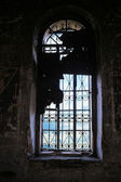Window with lattice in the old thrown temple — Стоковое фото
