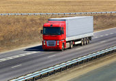 Trailer with red awning moves on the highway — Stock Photo
