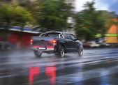 Pickup goes on the rainy city street — Stock Photo