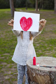 Young girl holding a hand-drawn painted red heart — Stock Photo