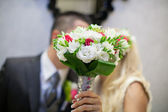 Wedding couple hugging, the bride holding a bouquet of flowers in her hand, the groom embracing her — Stock Photo