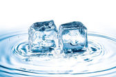 Ice cubes falling on water surface — Zdjęcie stockowe