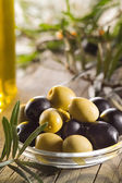 Green and black olives with leaves — Stock Photo