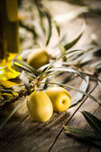 Organic olives with bottle of oil on a wooden table — ストック写真