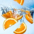 Orange fruits fall deeply under water with a big splash — Stock Photo