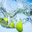 Green apples. Fruits fall deeply under water with a big splash — Stock Photo