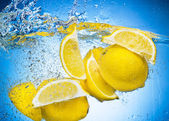 Lemon Slices falling deeply under water with a big splash on blu — Stock Photo