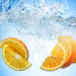 Stock Photo: Orange Slices falling deeply under water with big splash