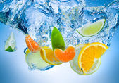 Tropical fruits fall deeply under water with a big splash — Stock Photo