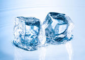 Ice cube on water surface — Stock Photo