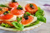 Green salad made with arugula, tomatoes, cheese mozzarella balls and sesame on plate, isolated on white — Stock Photo