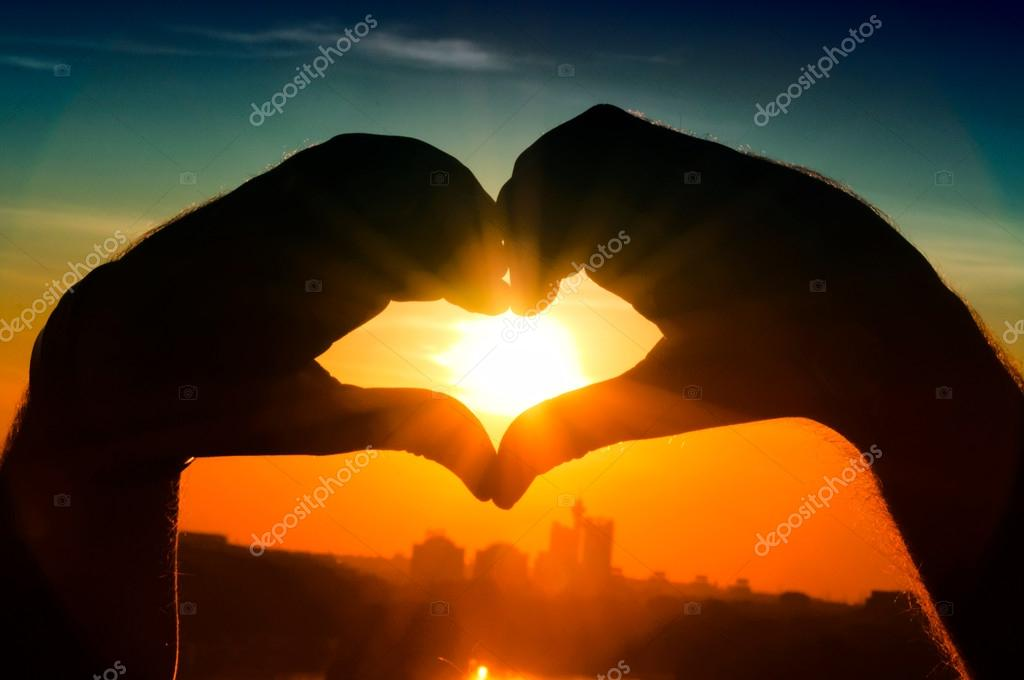 Hands showing the heart in back light — Stock Photo #13516616