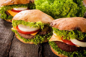 Three cheeseburgers on the table — Foto de Stock