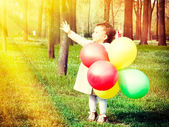 Little child holding the balloons — Stok fotoğraf