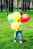 Child holding balloons — Stock Photo