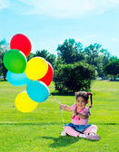 Child with balloons on the field — 图库照片
