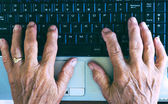 Old hands typing on computer keyboard — Stock Photo