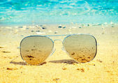 Aviator sunglasses on beach — Stock Photo