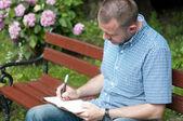 человек, писать в блокноте — Стоковое фото