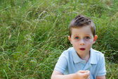 Little boy in a grass field with a blank expression — Stock Photo