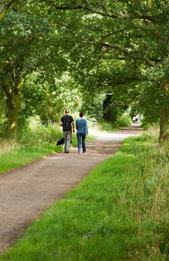 Young couple walking their dog along a country path — Stock Photo #12596642
