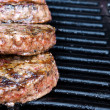 Beef quarterpounder burgers begin to cook on the gas barbecue — Stock Photo