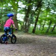 Boy riding bike through woods — Stock Photo