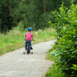 Boy riding bike through woods — Stockfoto