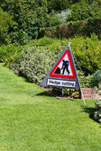 Hedge cutting sign in country garden — Stock Photo