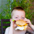 Little boy eating a huge burger — Stock Photo