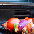 Stock Photo: Chicken and pepper kebabs slowly cooking on barbecue