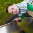 Stock Photo: Little boy sliding down side at park