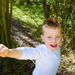 Little boy smiling in the woods - Stock Photo