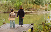 Brothers looking out across a pond in Autumn — Stock Photo