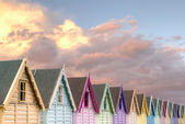 Row of beach huts red sky — Stock Photo