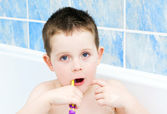 Little boy in the bath tub brushing his teeth — Stock Photo