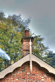 Chimney smoke coming from an old fashioned house — Stock Photo