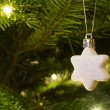 Christmas star hanging on the christmas tree — Stock Photo