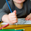 Young boy drawing with pencils on a table — Stock Photo