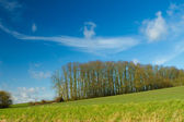 Hill in a green field in english countryside — Stock Photo