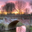 Stock Photo: River flowing through an english countryside scene at sunset