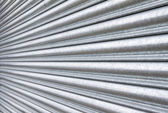Silver metal roller security shutters closed down — Stock Photo