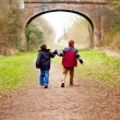 Stock Photo: Brothers holding hands together on country path