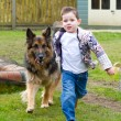 Little boy running with his pet german shepherd — Stock Photo